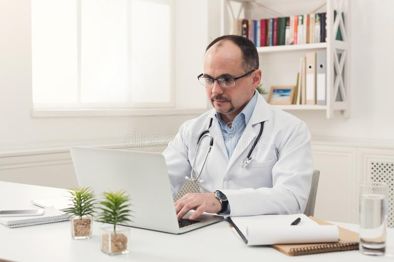Serious doctor in glasses typing on laptop stock photos