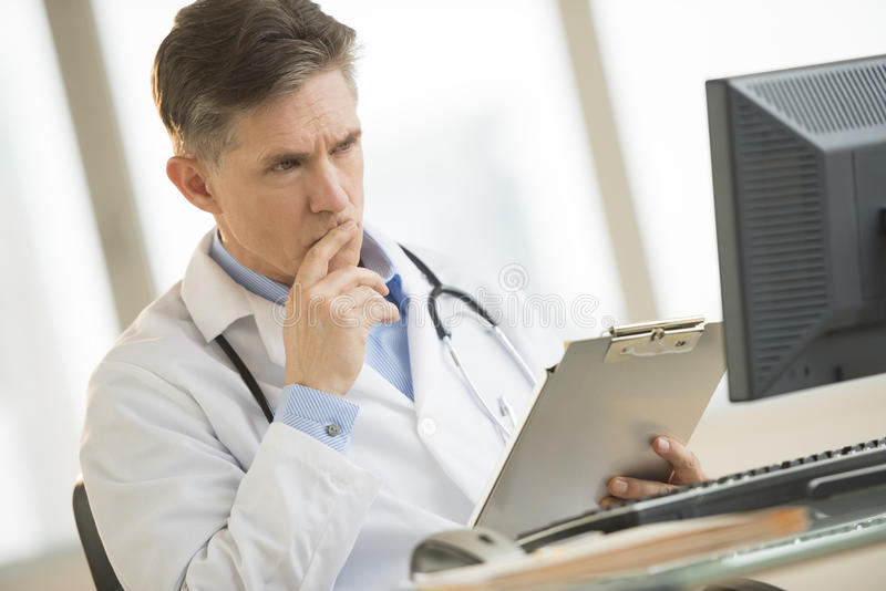 Serious Doctor Looking At Computer While Holding Clipboard At De royalty free stock photos