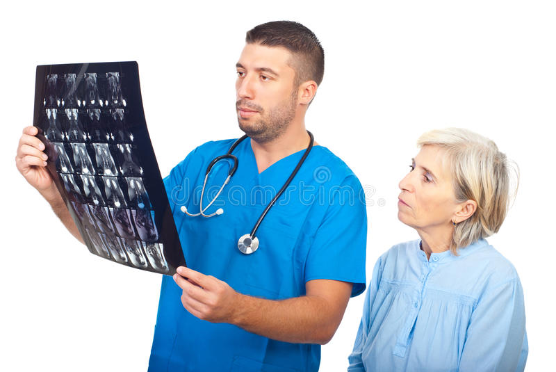 Serious doctor man showing MRI to patient. Serious doctor man showing results of magnetic resonance imaging to a senior patient and both being worried isolated royalty free stock photography