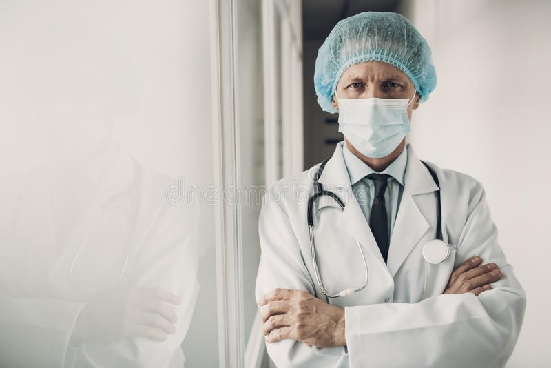 Serious Doctor in Mask and Cap with Crossed Arms royalty free stock photos