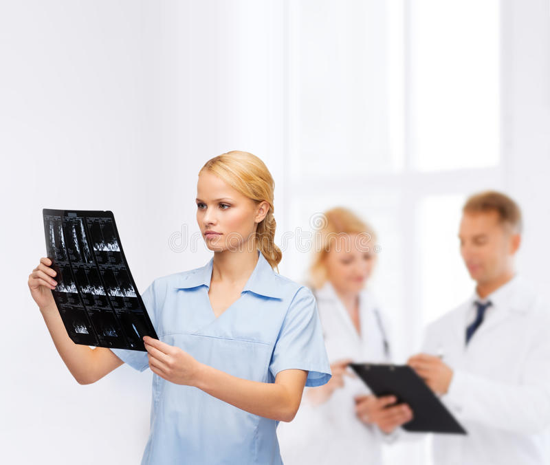 Serious doctor or nurse looking at x-ray. Healthcare, medicine and radiology concept - smiling doctor or nurse looking at x-ray stock image