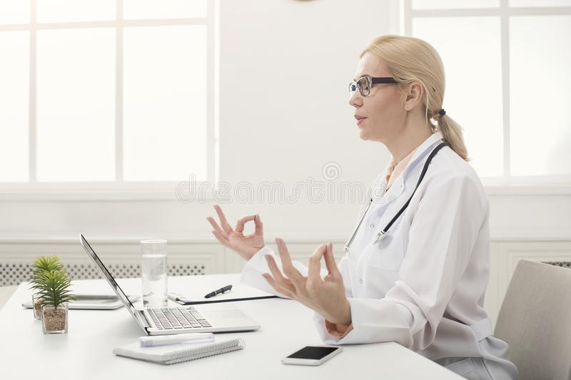 Serious doctor relaxing in her office royalty free stock image