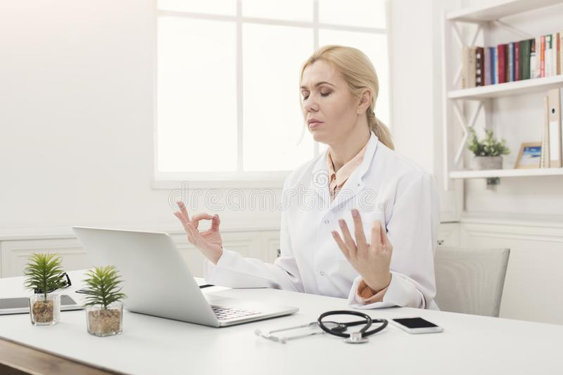 Serious doctor relaxing in her office royalty free stock photography