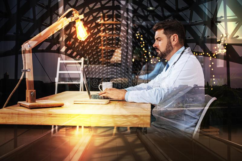 Serious doctor sitting alone and working on his modern device. Working alone. Calm clever experienced doctor sitting at the table in his comfortable office and royalty free stock images
