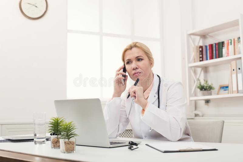Serious doctor talking on phone with patient stock images