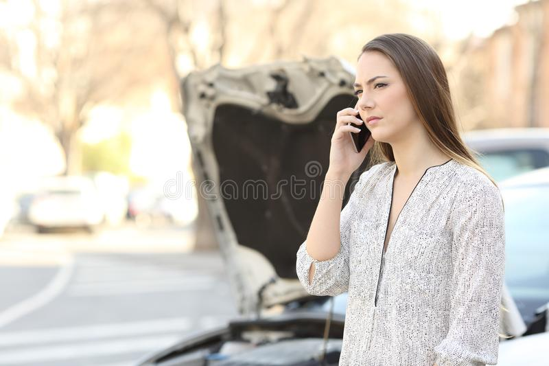 Driver with broken down car calling insurance on phone. Serious driver with a broken down car calling insurance on phone on the street royalty free stock photo