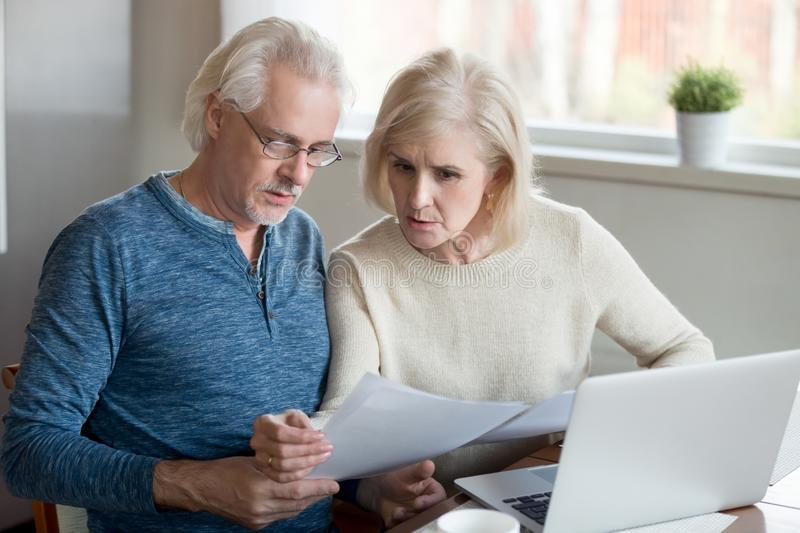 Serious elder husband and wife read bank documents at home. Serious aged husband and wife manage utility bills using laptop at home, concerned senior couple read stock photo