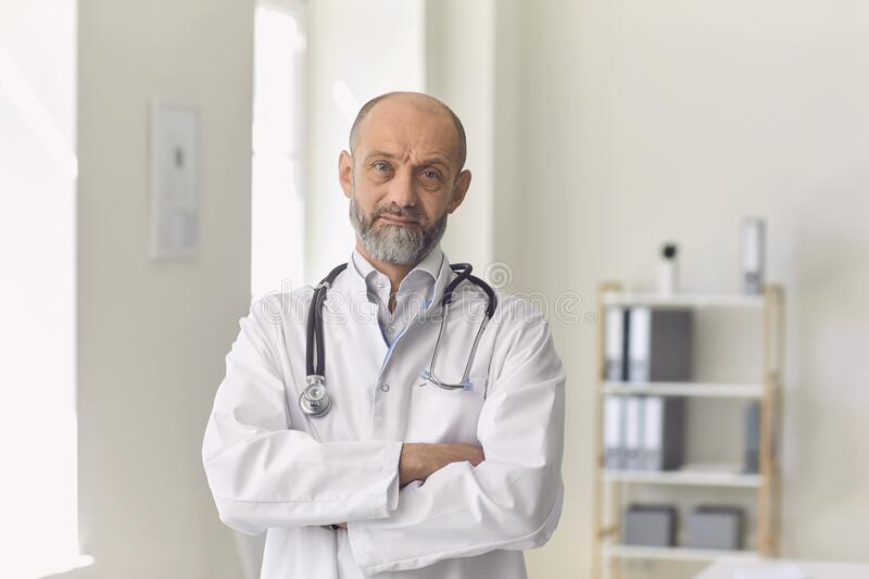 Serious elderly doctor in uniform looking at camera during online consultation with client in clinic royalty free stock photos