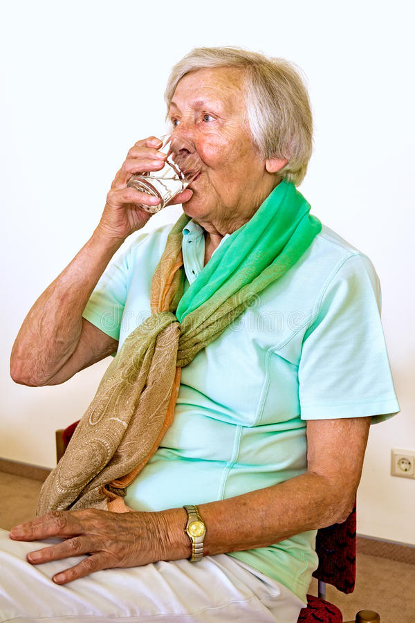 Serious elderly woman drinking water royalty free stock photo