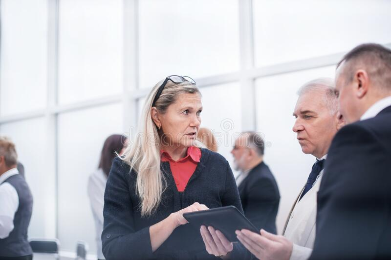 Serious employees discussing business document before meeting. royalty free stock photo