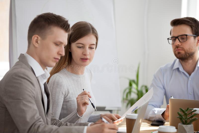 Serious employees talk collaborating at business meeting. Serious millennial colleagues talk analyzing company document or financial statistics, focused stock image