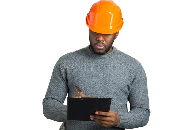 Serious engineer writing on clipboard. royalty free stock photo