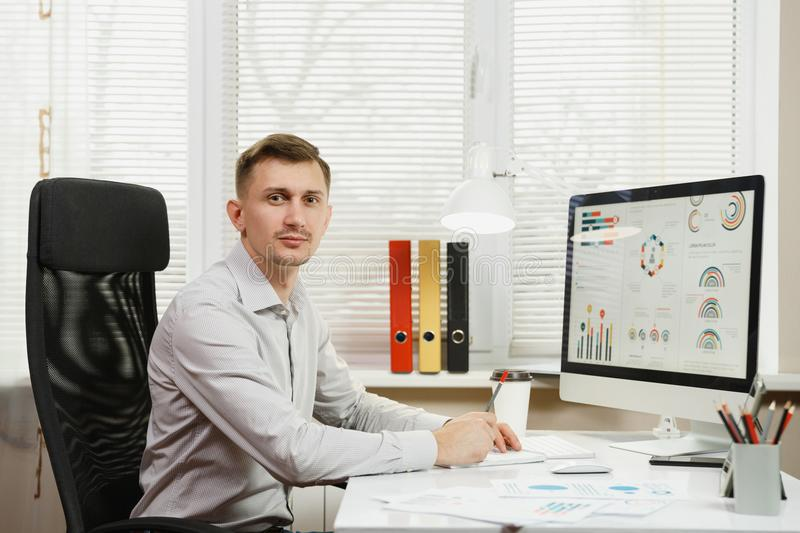 Serious and engrossed business man in shirt sitting at the desk, working at computer with modern monitor. Manager or worker. stock image