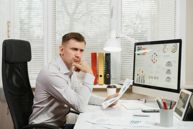 Serious and engrossed business man in shirt sitting at the desk, working at computer with modern monitor. Manager or worker. royalty free stock photos