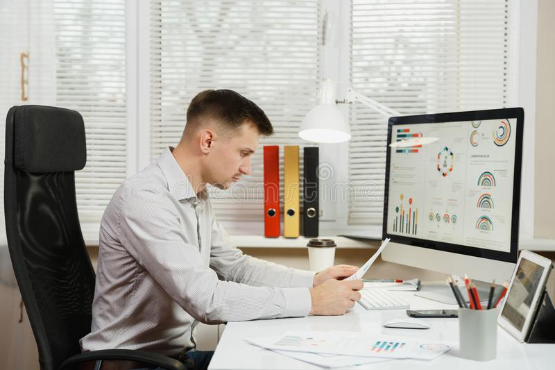 Serious and engrossed business man in shirt sitting at the desk, working at computer with modern monitor. Manager or worker. stock photos