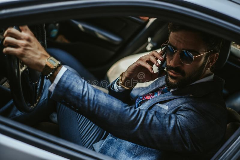 Entrepreneur driving the car and talking on the mobile phone stock photos