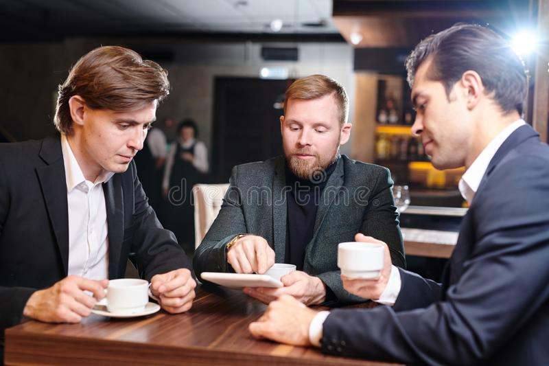 Serious entrepreneurs analyzing report on tablet in cafe royalty free stock photos