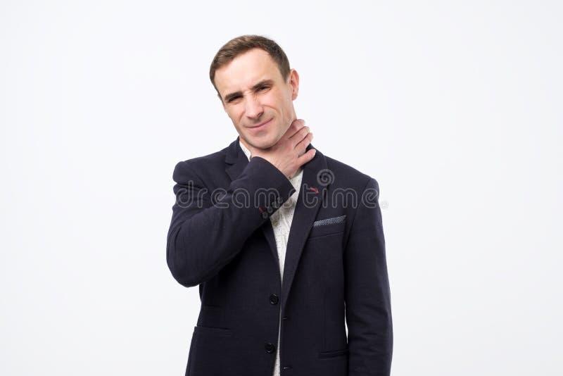 Serious european man in suit having pain in throat. royalty free stock photo