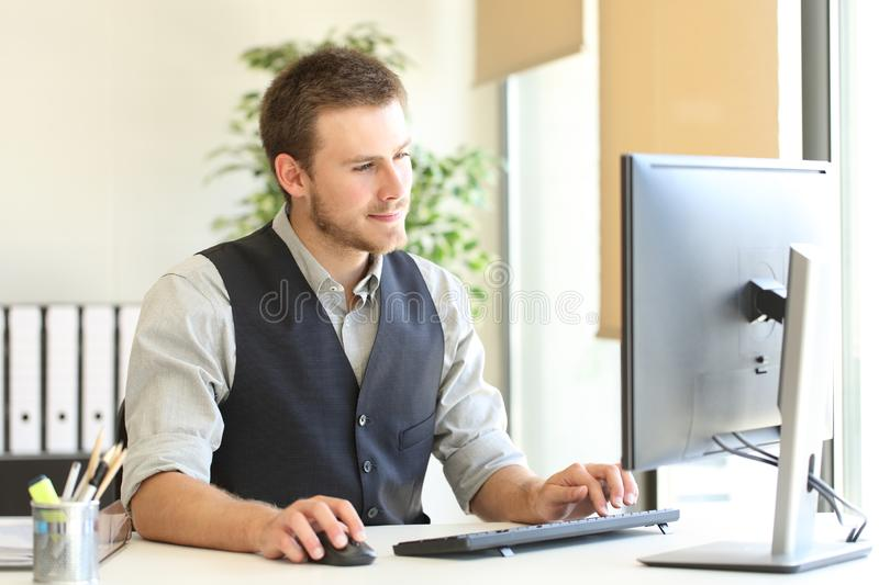 Serious executive browsing computer content at office royalty free stock images