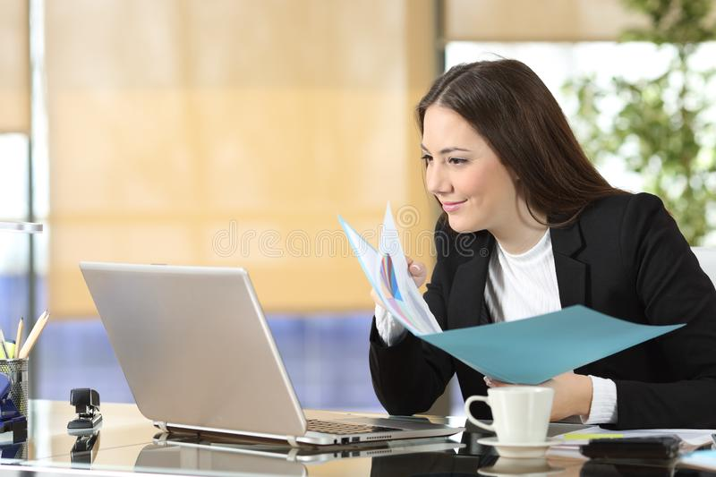 Serious executive comparing laptop content and documents stock photos