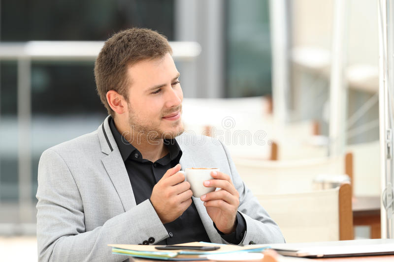 Serious executive thinking in a coffee shop royalty free stock image