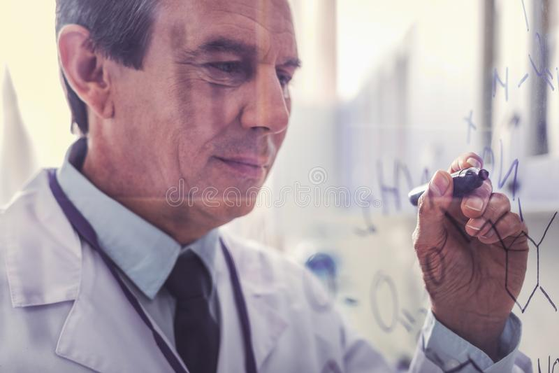 Serious experienced chemist creating new chemical formula. Experienced chemist. Serious experienced chemist feeling inspired while creating new chemical formula stock photos