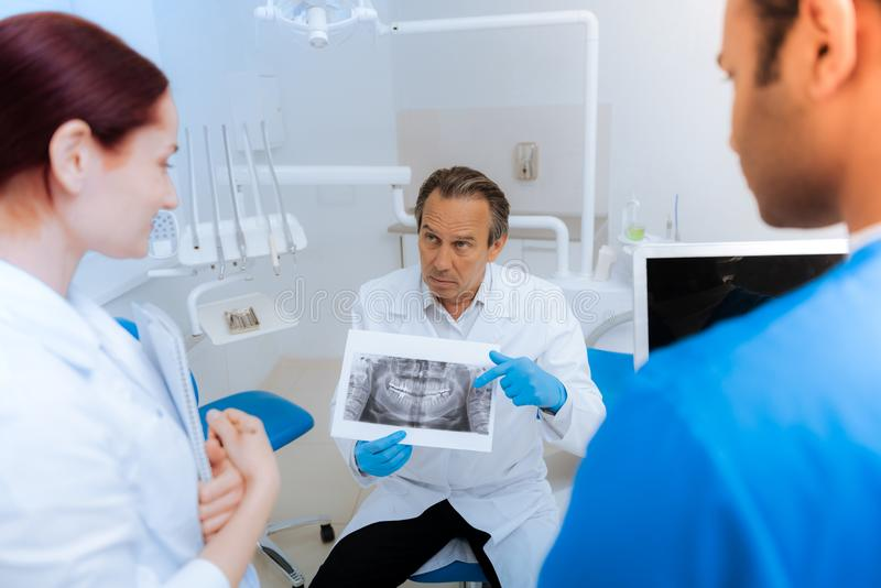 Serious experienced dentist pointing at the X ray scan. What do you think. Serious hard working experienced dentist holding an X ray scan and pointing at it royalty free stock image