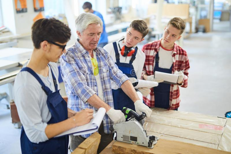 Serious carpenter sawing wooden plank at woodworking class stock photo