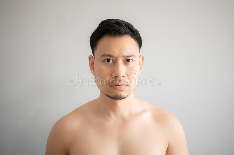 Serious and stress face of Asian man in topless portrait isolated on gray background royalty free stock photo