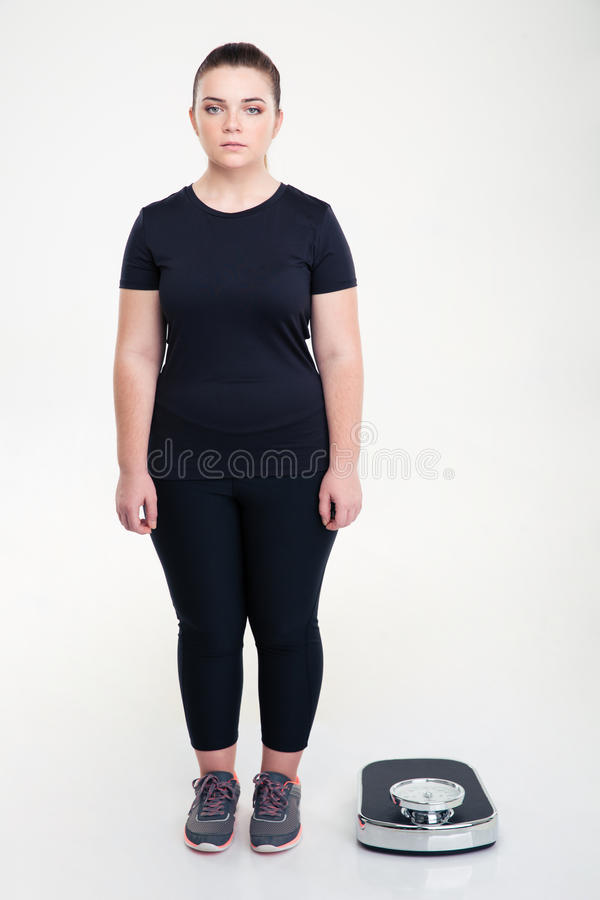 Serious fat woman standing near weighing machine. Full length portrait of a serious fat woman standing near weighing machine isolated on a white background royalty free stock images