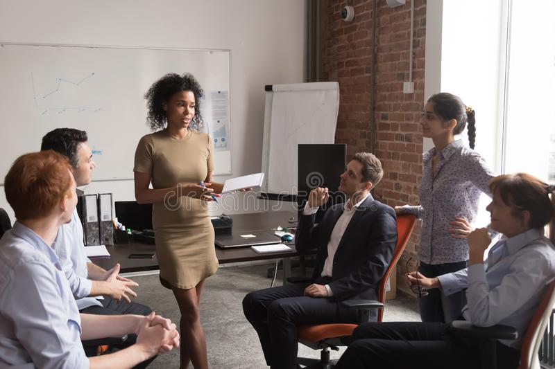 Serious female african coach mentor speaking at diverse team meeting royalty free stock image