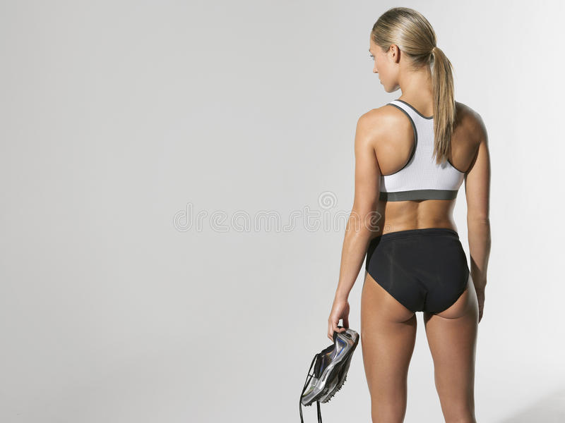 Serious Female Athlete Holding Shoes royalty free stock photography