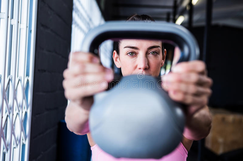 Serious female athlete lifting kettlebell in gym stock photos