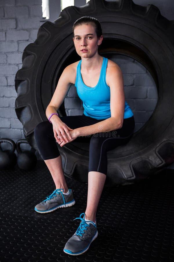 Serious female athlete sitting on tire stock image
