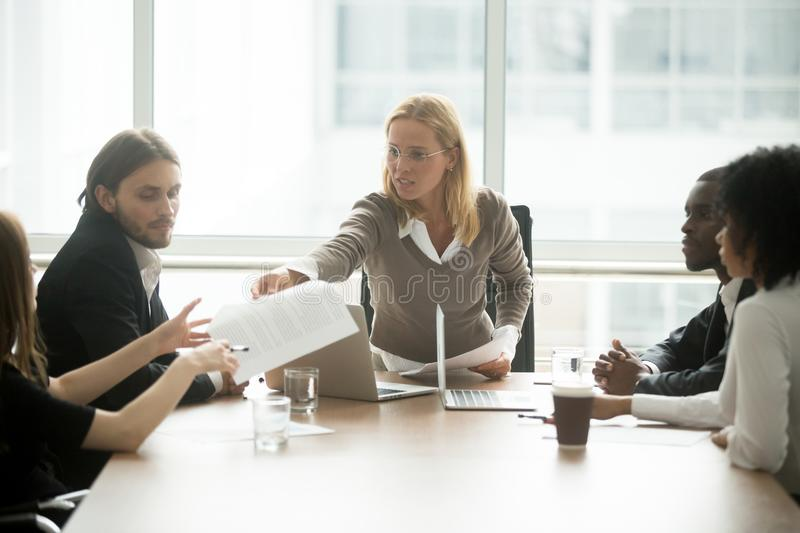 Serious female boss handing paper report to employee at meeting royalty free stock photos