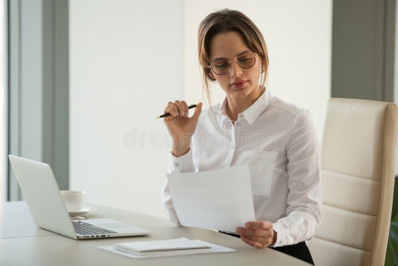 Serious female boss reading document analyzing statistics stock photos