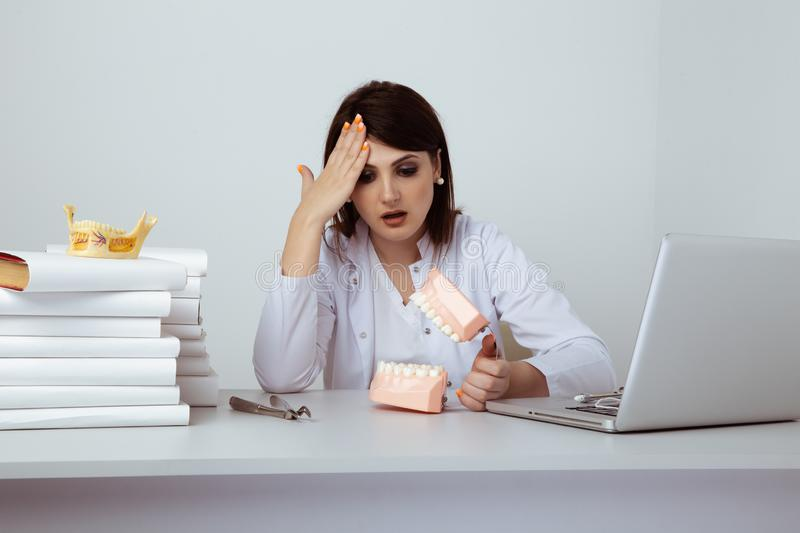 Serious female dentist sitting and working with dental staff isolated. royalty free stock image