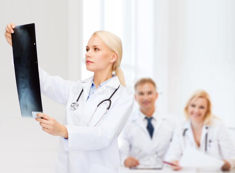 Serious female doctor looking at x-ray. Healthcare, medicine and radiology concept - serious female doctor looking at x-ray stock photography