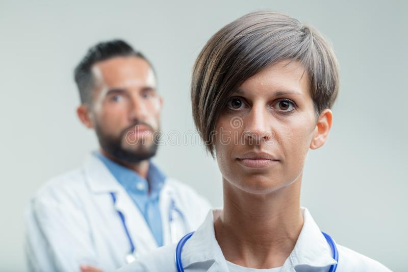 Serious female doctor or nurse in a medical team stock images