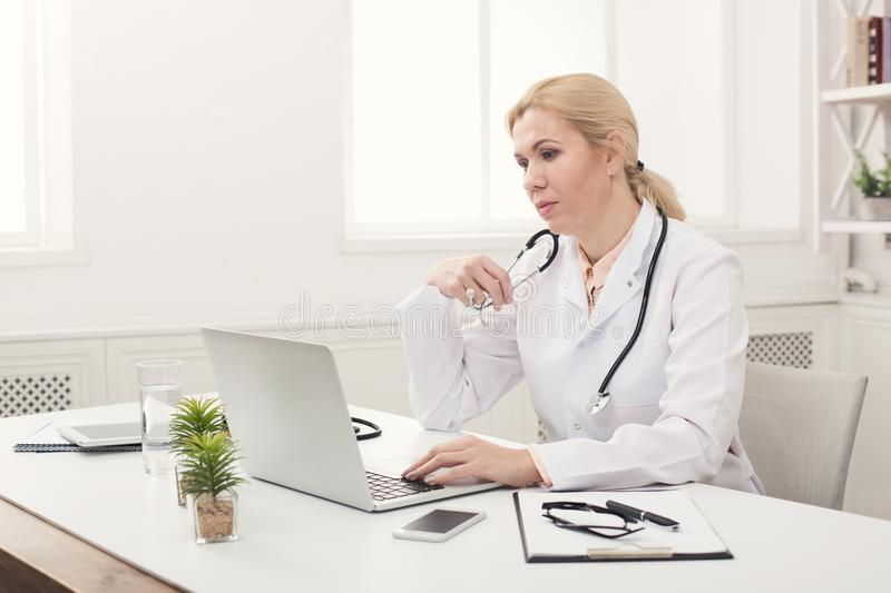 Serious female doctor typing on laptop royalty free stock photo