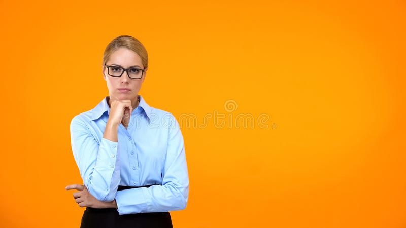 Serious female with hand on chin looking camera, work problem, business choice royalty free stock photo