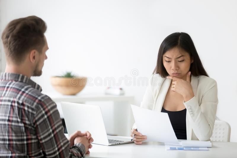 Serious Asian employer reading cv doubting in employees candidat stock image