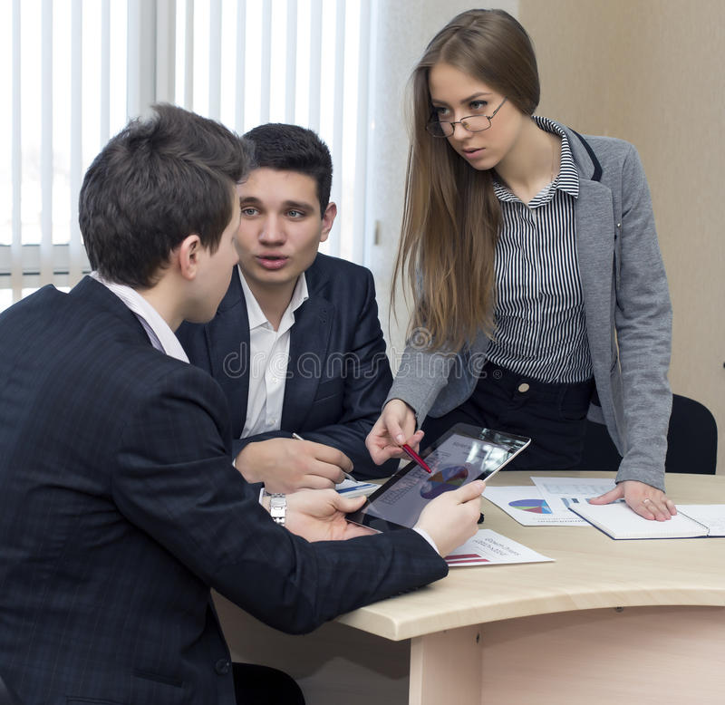 Serious female manager explains corporate data to. Her associate Group of business people discuss the data using tablet pc and paper charts and presentations stock photography