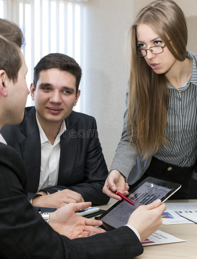 Serious female manager explains corporate data to. Her associate Group of business people discuss the data using tablet pc and paper charts and presentations royalty free stock photos