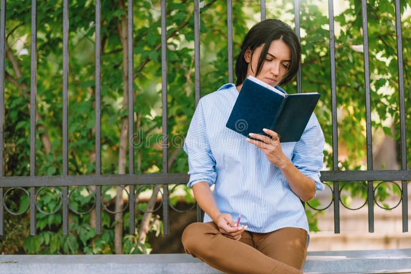Serious female model focused on reading, sits at wall in the park. Concetrated student prepares for coming session at college. stock image