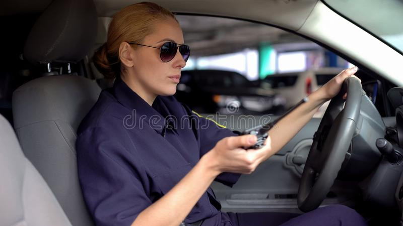 Serious female officer holding radio set and driving car, emergency situation royalty free stock photos