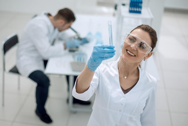 Serious female scientist looks at the tube with the results of the analysis stock photo