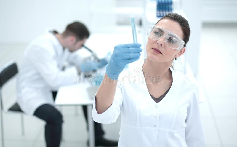 Serious female scientist looks at the tube with the results of the analysis royalty free stock photography