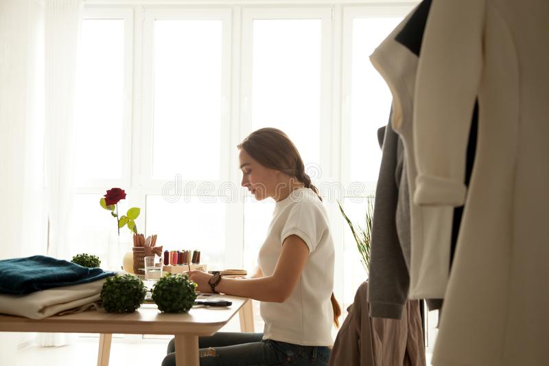 Serious fashion designer creating new collection in her studio stock photos