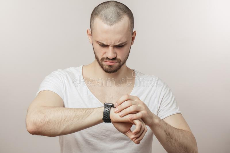 Serious fit, sporty man is looking at the smartwatch. Man has missed the workout in the morning. broken watch royalty free stock photography